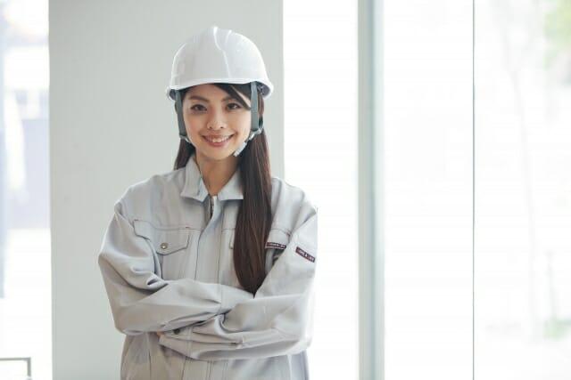 腕を組む作業員姿の女性