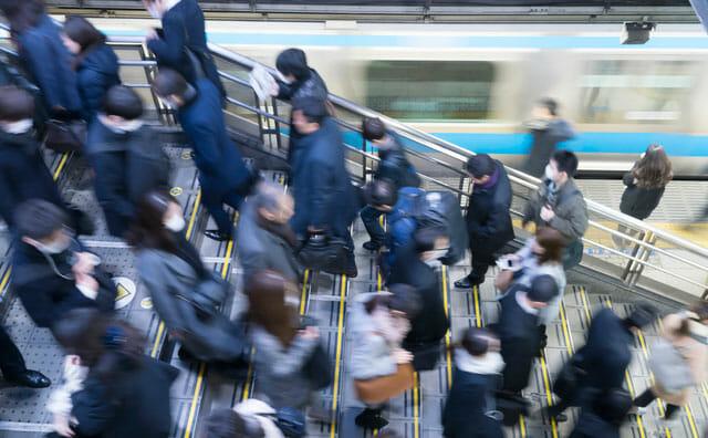 マスクをして通勤する人々