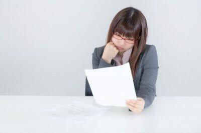 紙を前に悩む女性の写真