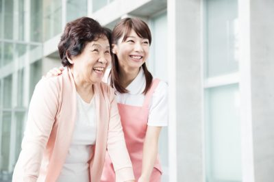 介護士が女性の高齢者を支える写真