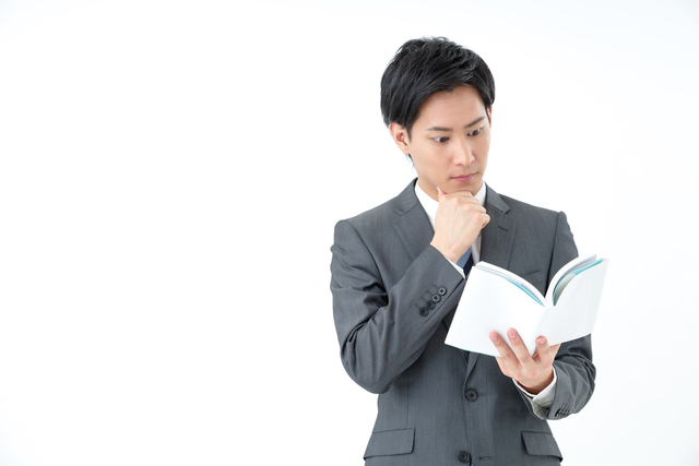 本を読んで悩む男性の写真