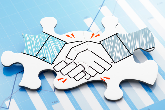 Handshake jigsaw puzzle pieces on blue chart.