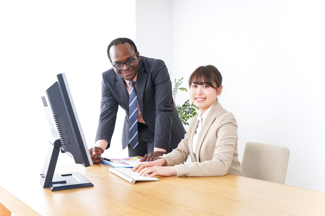 外国人と一緒に働く女性の写真